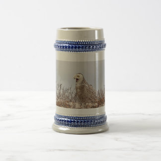 Snowy owl sitting on the beach beer stein