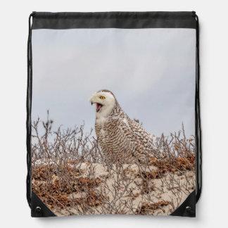 Snowy owl sitting on the beach drawstring bag