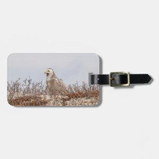 Snowy owl sitting on the beach luggage tag