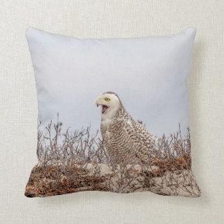 Snowy owl sitting on the beach throw pillow