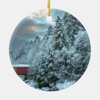 Snowy pines above a covered bridge round ornament