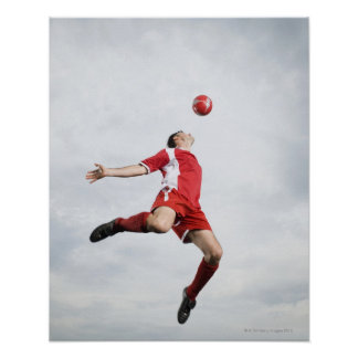 Soccer player and soccer ball in mid-air poster
