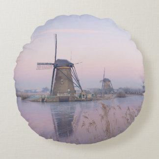 Soft sunrise light in winter over windmills round pillow