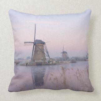 Soft sunrise light in winter over windmills throw pillow