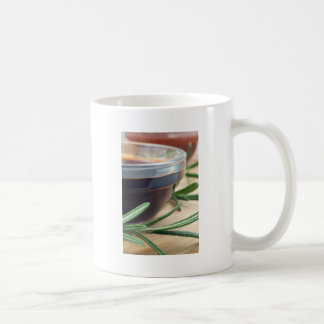 Soy sauce in a glass and a sprig of rosemary coffee mug