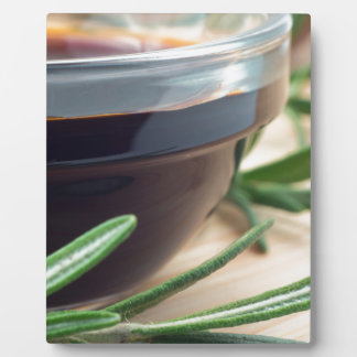 Soy sauce in a glass and a sprig of rosemary plaque