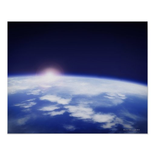 Space with rising sun above planet earth posters