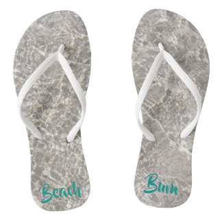 Sparkeling water on sand beach bum flipflops