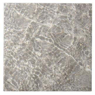 Sparkeling water on sand ceramic tile