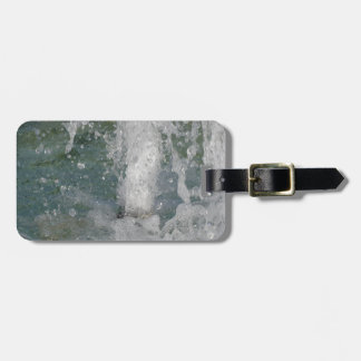 Splashes of fountain water in a sunny day luggage tag