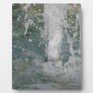 Splashes of fountain water in a sunny day plaque