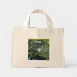 Splashing duck in a pond mini tote bag