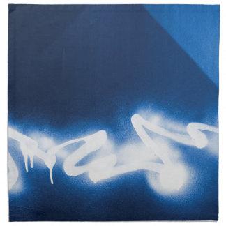 Sprayed graffiti on blue metal cloth napkin