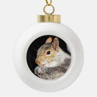 Squirrel eating a nut ceramic ball ornament