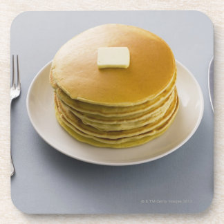 Stack of pancakes with butter on a plate coasters