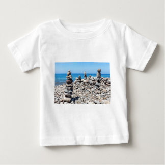 Stacked beach stones at blue sea baby T-Shirt