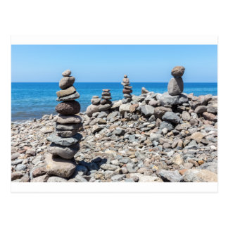 Stacked beach stones at blue sea postcard
