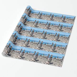 Stacked beach stones at blue sea wrapping paper