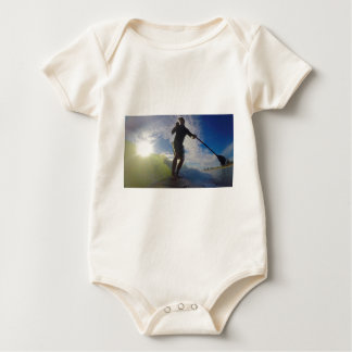 Stand up paddle board surfing a wave baby bodysuit