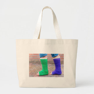 Standing child with two colorful gypsum legs large tote bag