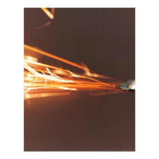 Steel tool on a grinder with sparks letterhead