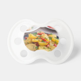 Stewed potatoes with bell pepper closeup baby pacifiers