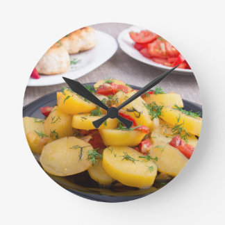 Stewed potatoes with bell pepper closeup round clock