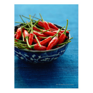 Still life of chilies in bowl on blue mat postcard