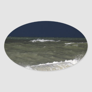 Stormy sea with waves und a dark blue sky. oval sticker