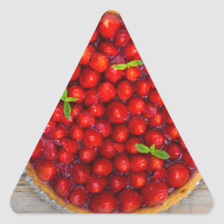 Strawberry cake with mint leaves on a rustic wood triangle sticker