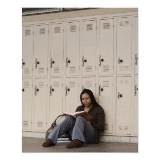 Student leaning on school lockers studying poster
