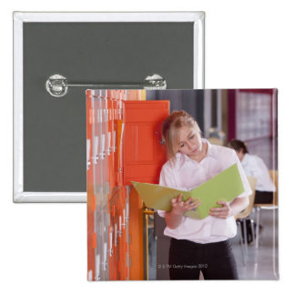Student removing binder from school locker 2 inch square button