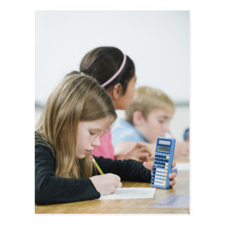 Students doing math work in classroom postcard