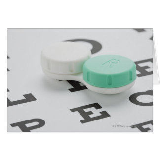 Studio shot of contact lens case on eye chart greeting card
