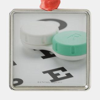 Studio shot of contact lens case on eye chart metal ornament
