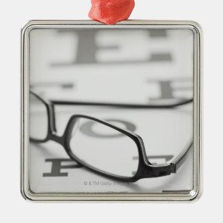 Studio shot of eyeglasses on eye chart metal ornament