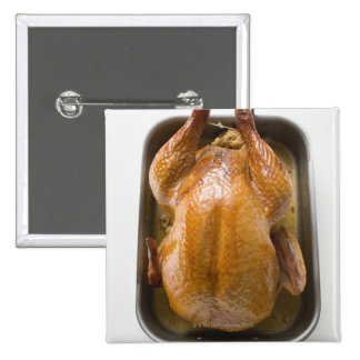 Stuffed roast turkey in roasting tray, close up 2 inch square button