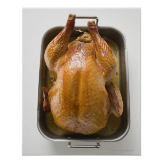 Stuffed roast turkey in roasting tray, close up poster