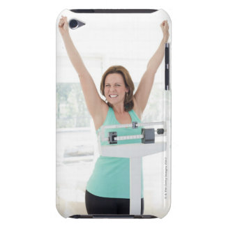 Successful weight loss. Happy woman weighing Barely There iPod Cases