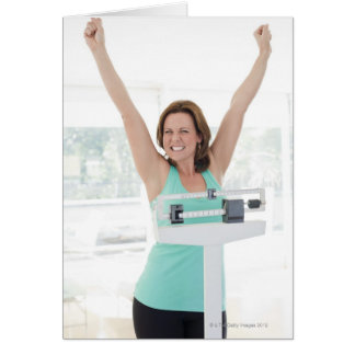 Successful weight loss. Happy woman weighing Greeting Cards