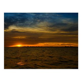 Sun setting down behind the city postcard