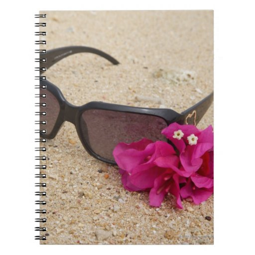 Sunglasses and bougainvillia flowers on coral notebook