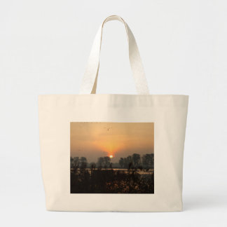 Sunrise at a lake with flying birds. large tote bag