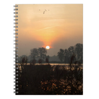 Sunrise at a lake with flying birds. spiral notebook