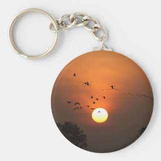 Sunrise with flocks of flying cranes keychain