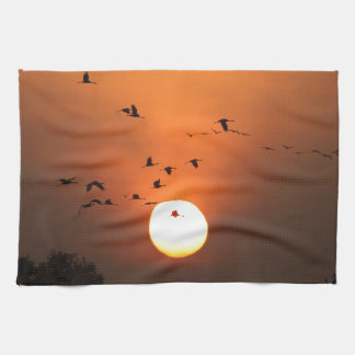 Sunrise with flocks of flying cranes towels