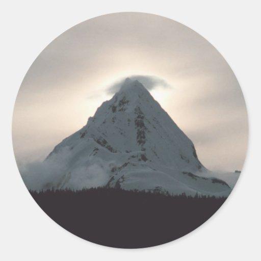 Sunset behind a snowy mountain round sticker