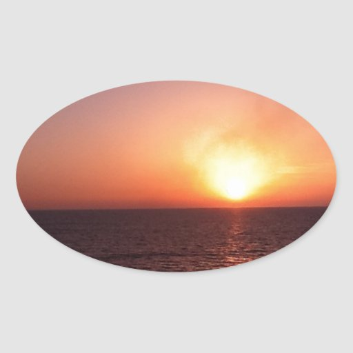 Sunset over the sea oval sticker