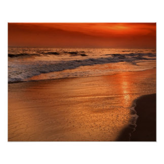 Sunset reflections off clouds and ocean shore poster