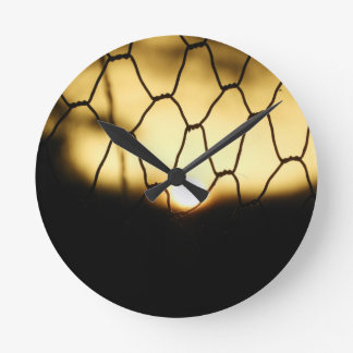 Sunset through the fence round clock